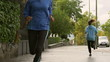 Women jogging and man stretching, slow motion shot, steadycam sh