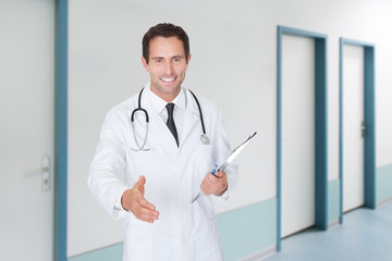 Confident Doctor Offering Handshake While Holding Clipboard