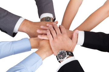 Businesspeople's Hands On Top Of Each Other Symbolizing Unity
