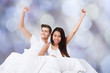 Successful Couple With Arms Raised On Bed