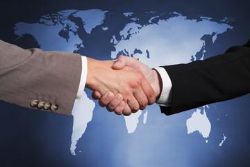 Businessmen Shaking Hands Against Worldmap