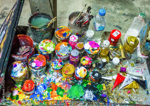 Brushes and cans of paint on a multicolored palette © SimoneGilioli