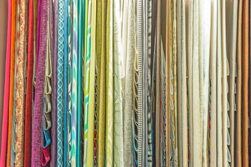 Colorful curtain samples hanging from hangers on a rail in a dis