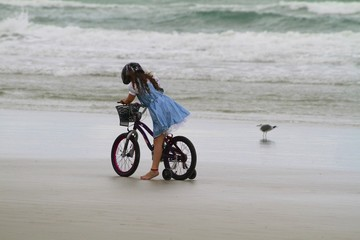 Little Girl riding on her bike at the beach