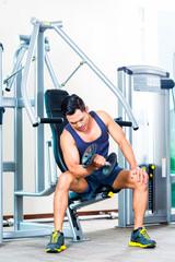 Asian man lifting hand weight at gym