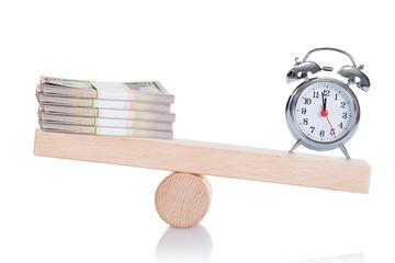 Alarmclock And Dollar Bundles Balancing On Seesaw