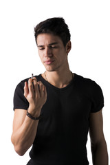 Young man disgusted by cigarette he's holding in his hand