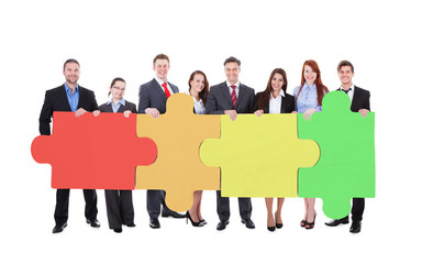 Confident Businesspeople Joining Jigsaw Puzzle Pieces