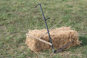 Rake and scythe in the garden left on a straw bale