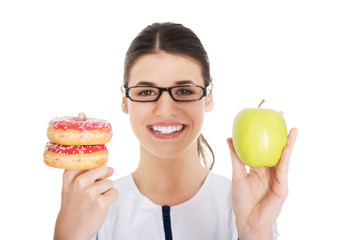Nutritionist holding a cake and apple