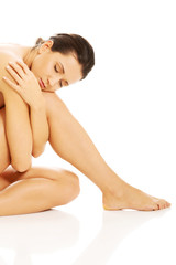 Nude woman embracing her legs