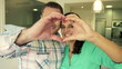 Portrait of happy couple showing heart symbol with hands at home
