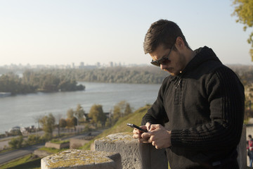 Handsome Man Sending Message On Mobile Phone Outdoor