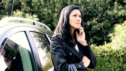 Young woman talking on cell phone in front of her car
