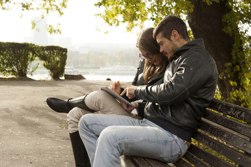 Happy Couple Using Tablet Computer On Bench Outdoor