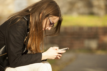 Pretty Girl Using Mobile Phone On Bench Outdoor
