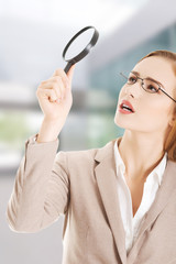 Beautiful business woman with magnifying glass.