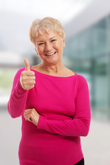 Old woman wearing pink shirt, showing OK.