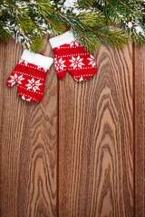 Christmas mitten decor and snow fir tree over wooden background