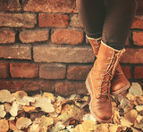 Fototapety Conceptual image of legs in boots on the autumn leaves - Walking