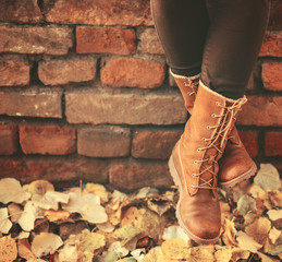 Conceptual image of legs in boots on the autumn leaves - Walking