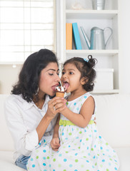 indian mother and child enjoying ice cream indoor