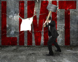 businessman holding sledgehammer hitting red LIMIT word on concr