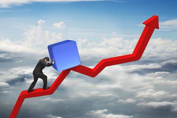 businessman pushing blue 3D block upward on red trend line