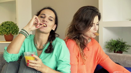 Two female girlfriends sharing cookie and raising toast on sofa