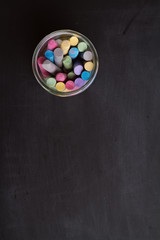 Overhead of chalkboard and jar of colored chalk
