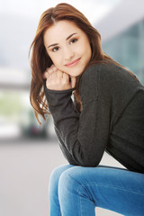 Portrait of young casual woman sitting