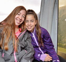 Portrait of two sisters hugging in a cable car