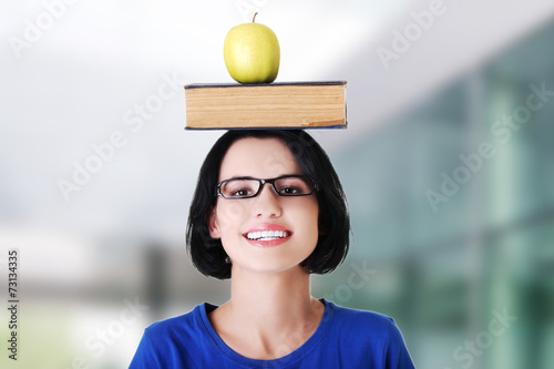 canvas print picture Woman holding an apple on head