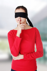 Blindfold woman with finger on lips.