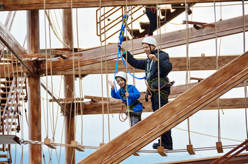 Boy and his father enjoying a challenging rope course