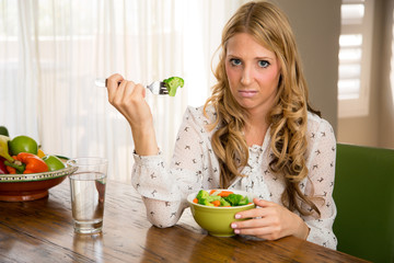 Unhappy woman eating healthy vegies