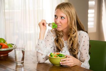 Woman smelling her boring healthy vegan food
