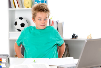 boy with exercise book and PC on tesk