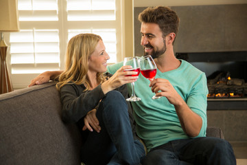 Attractive couple toasting with wine at home