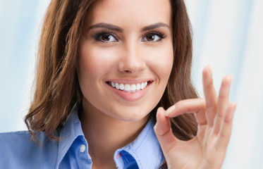 Businesswoman showing okay gesture, at office
