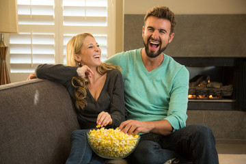 Husband and wife watching tv and eating popcorn at home