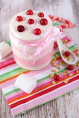 Raspberry milk dessert in glass jar,