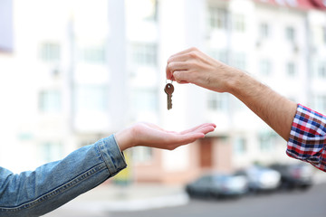 Man and woman hands hold keys near apartment house
