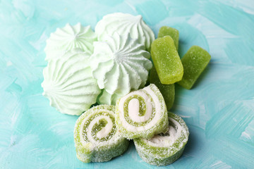 Mint color meringues and mint jelly candies on color background