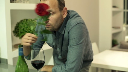 Sad, lonely romantic man waiting for his date and drinking wine
