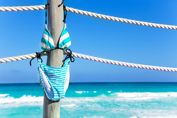 Swimming suit hanging on the white ropes of pier