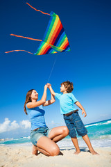 Beautiful woman and boy holding arms with kite