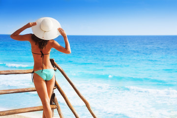 Back of beautiful girl on pier holding white hat