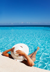 Lady with white hat relaxes in swimming pool