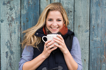 Smiling fashionable blonde drinking hot beverage
